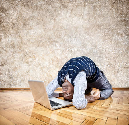 working animal: Indian businessman doing yoga and looking at his laptop in the office at brown textured background