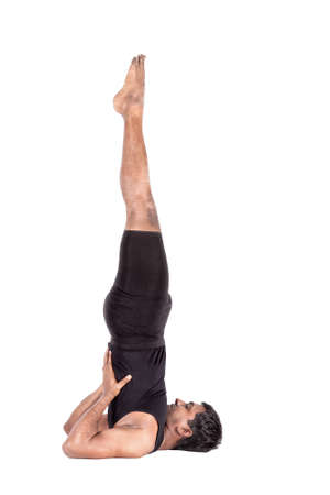 Yoga salamba sarvangasana shoulder stand pose by Indian man in black costume isolated at white background. Free space for text photo