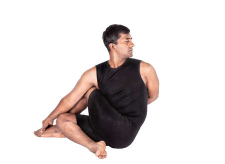 Yoga ardha matsyendrasana half spinal twist pose by Indian man in black costume isolated at white background. Free space for text Stock Photo