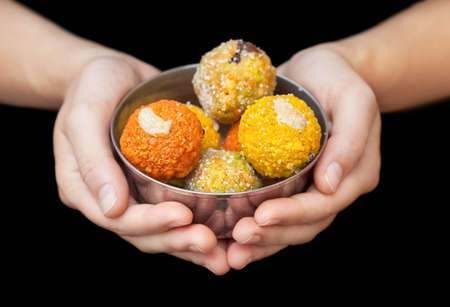 Woman holding Indian traditional sweets ladu in metal bowl at black background photo