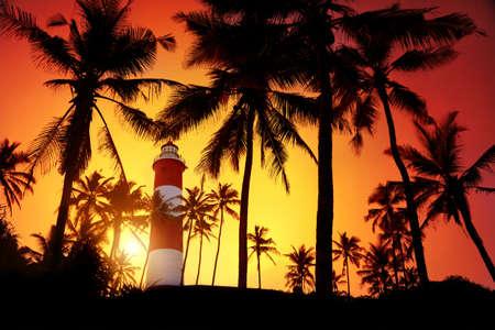 kovalam: Lighthouse around palm trees at orange sunset sky in Kovalam, Kerala, India