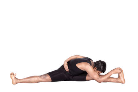 Yoga variation of Upavistha konasana pose by Indian man in black costume isolated at white background. Free space for text photo