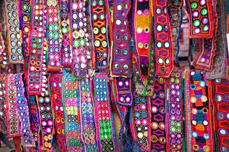 atc: Colorful ethnic belts with mirrors at Anjuna flea market in Goa, India