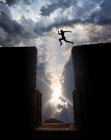 saltando: Silueta del hombre que salta sobre el abismo al atardecer nublado cielo de fondo