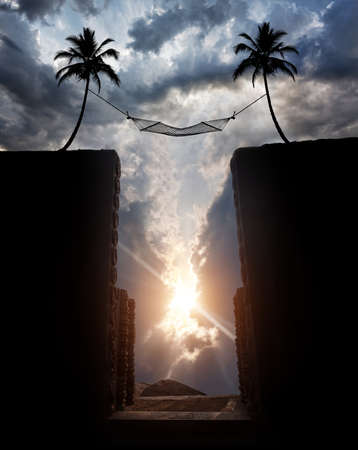 Silhouette of Hammock hanging over the abyss on palm trees at sunset cloudy sky background photo