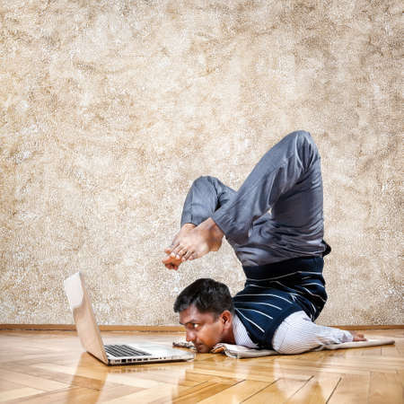 Indian businessman doing yoga and looking at laptop in the office at brown textured background Stock Photo - 19608969