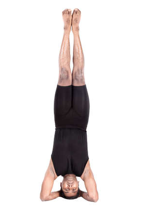 Yoga headstand pose by Indian man in black costume isolated at white background photo