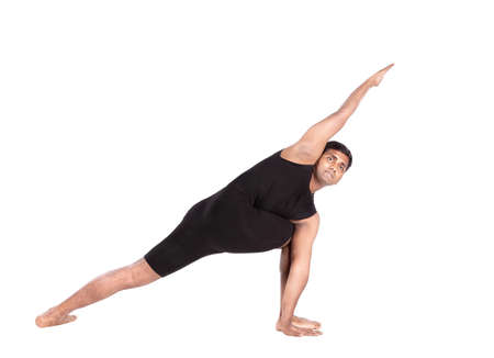 Yoga pose by Indian man in black costume isolated at white background photo