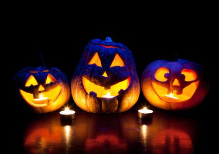 carving pumpkin: Scary calabazas de Halloween con los ojos brillando adentro en el fondo negro