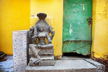 mamallapuram: Stone Goddess near grunge yellow wall and green door in Mamallapuram cave, Tamil Nadu, India
