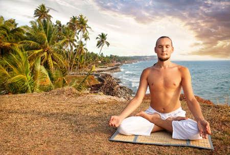 dhyana: Meditazione yoga nella posizione del loto con l'uomo in pantaloni bianchi sulla scogliera vicino al mare in Kerala, India