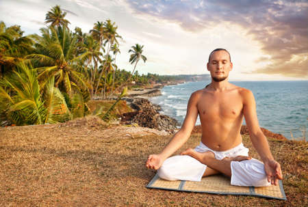 tree position: Yoga meditation in lotus pose by man in white trousers on the cliff near the ocean in Kerala, India Stock Photo