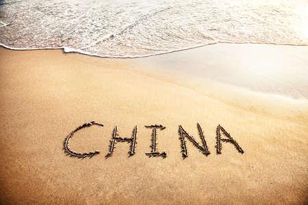China title on the sand beach near the ocean photo