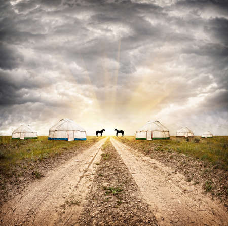 nomadic: Nomadic village with yurts and horses at dramatic overcast sky with sun in steppe in Asia Stock Photo