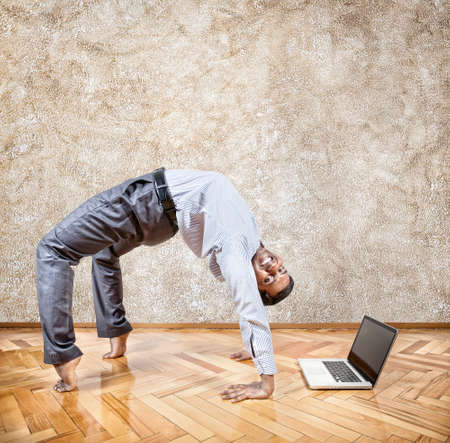 Happy Indian businessman doing yoga nearby laptop in the office at brown textured background Stock Photo - 19751000