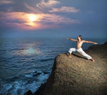 Yoga guerrero plantean por el hombre en pantalones blancos en el acantilado cerca del océano en Kerala, India Foto de archivo
