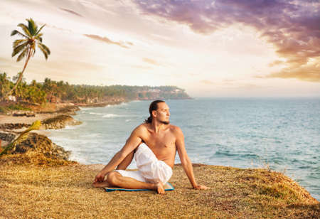 Yoga by man in white trousers on the cliff near the ocean in Kerala, India photo
