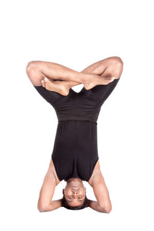 shirshasana: Yoga headstand pose in padmasana by Indian man in black costume isolated at white background. Free space for text Stock Photo