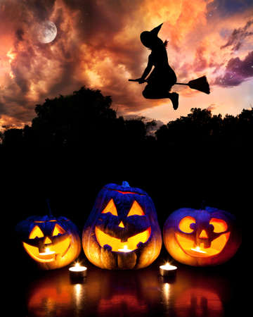 haloween: Halloween glowing pumpkins on the table and witch silhouette flying at dramatic night sky with moon