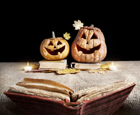 Halloween pumpkins reading old book at black background photo