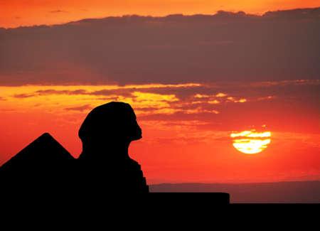 스핑크스와 이집트에있는 오렌지 일몰 하늘에서 피라미드의 실루엣 스톡 콘텐츠