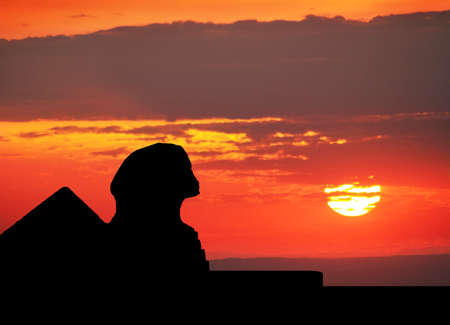 Sphinx  and Pyramids silhouette at orange sunset sky in Egypt