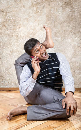 Indian businessman doing yoga and talking on the phone in the office at brown textured background photo