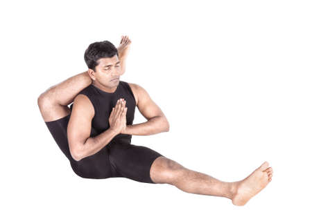 shirshasana: foot behind the head pose by Indian man in black costume isolated at white background