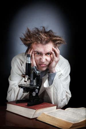 Thinking young professor in white coat with microscope and books photo