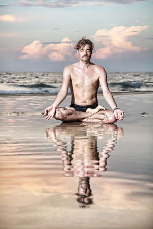 dhyana: Yoga meditation in lotus pose by man on the beach near the ocean in India Stock Photo