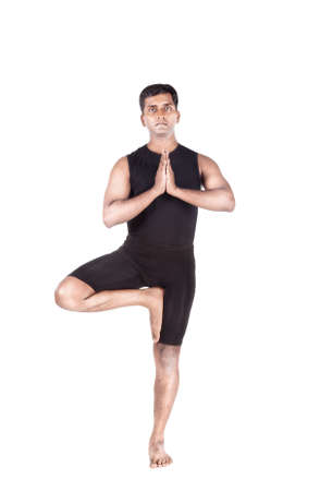 vriksasana: Yoga tree pose by Indian man in black costume mudra isolated at white background