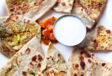 Vegetarian aloo paratha with curd and mango pickle in Indian restaurant