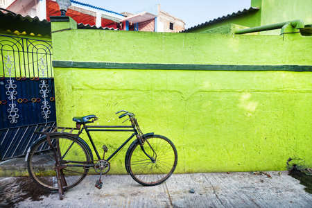 Bicycle near green wall on the street of Mamallapuram in Tamil Nadu, India photo