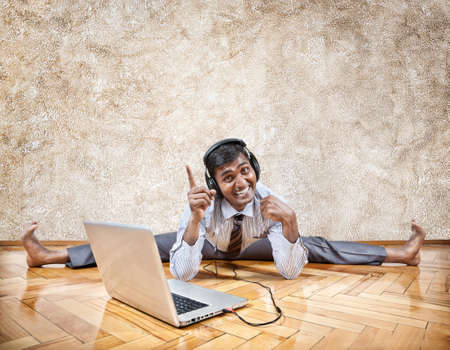 Indian businessman listening to the music with headphones and doing yoga near the laptop on the floor Stock Photo - 19983642
