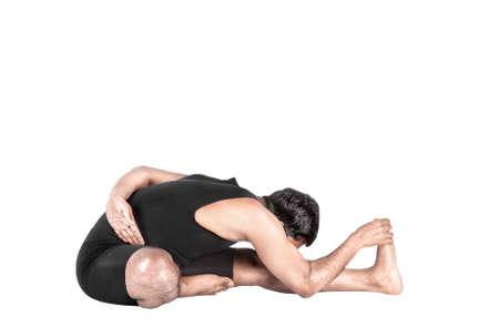 Yoga Janu Sirsasana forward bending pose by Indian man in black costume isolated at white background Stock Photo - 19983636