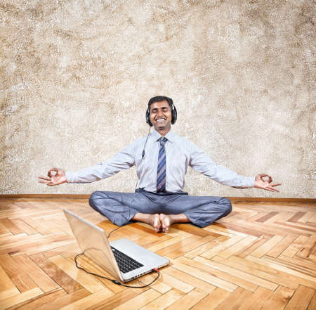 baddha: Indian businessman listening to the music with headphones and doing meditation near the laptop Stock Photo