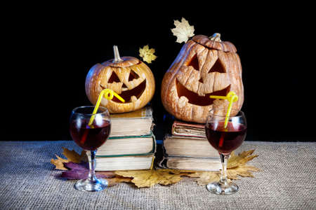Funny Halloween pumpkins drinking wine on the heap of books at black background photo