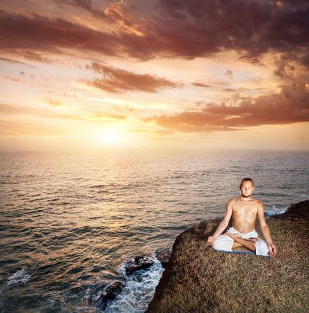 dhyana: Meditazione yoga nella posizione del loto con l'uomo in pantaloni bianchi sulla scogliera vicino al mare al tramonto in Kerala, India