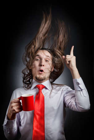 Funny man with hair up holding red mug and pointing up at black background photo