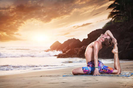 Yoga pigeon pose by man on the sandy beach near the ocean in India photo