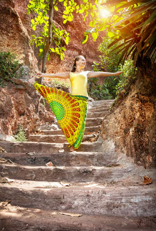 eka: Yoga by woman in Indian trousers on the stairs in Kerala, India