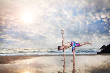 Yoga by man on the beach with reflection on the sand near the ocean in India