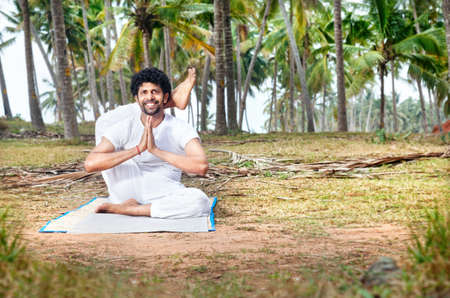 Yoga by happy Indian man in white trousers near palm trees in Kerala, India Stock Photo