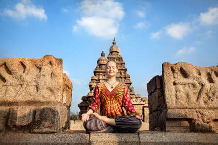 mamallapuram: Woman doing meditation in lotus pose near Shore temple, Mamallapuram, Tamil Nadu, India Stock Photo