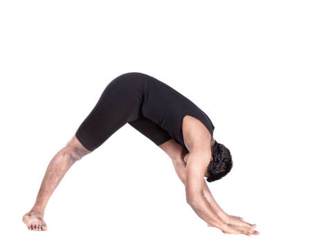 Yoga forward bending pose by Indian man in black costume isolated at white background photo