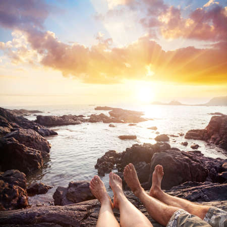Woman and man sitting on the rocks near the ocean at cloudy sunset sky photo