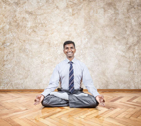 Happy Indian businessman doing meditation in the office Stock Photo - 20412425
