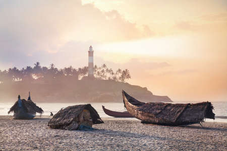 Fisherman boats on the beach in the morning at lighthouse background in Kovalam, Kerala, India