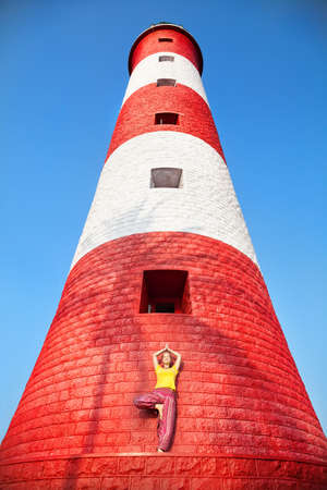vriksasana: Yoga tree pose by woman near red and white lighthouse at blue sky in Kovalam, Kerala, India Stock Photo