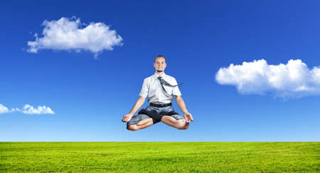 dhyana: Businessman doing Yoga meditation and levitating under the grass at blue sky with white clouds Stock Photo
